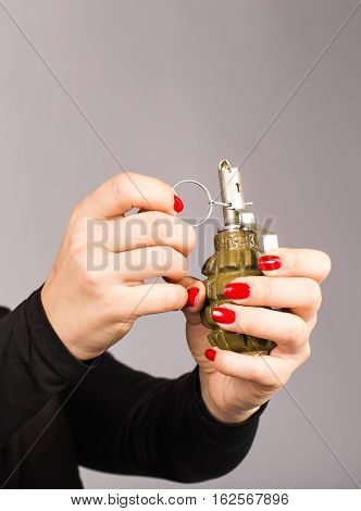 Hand grenade in a woman's hand with the pin pulled.