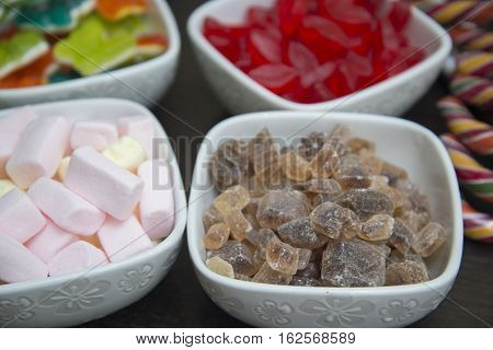Many different sweets are in white bowls. Children's happiness.