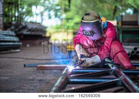 Welder with Flux Core Arc Welding process in steel structure in fabrication factory.