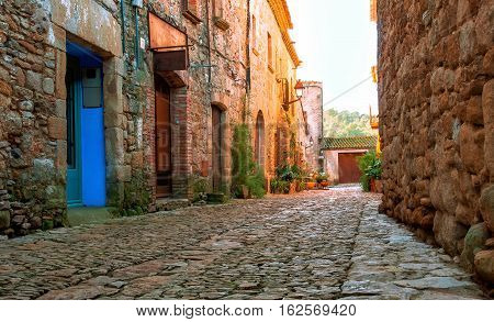 A street in the old town of Peratallada, Catalonia, Spain. Medieval street in the mediaval town in Europe.  Panoramic view of old town  in beautiful evening light at sunset