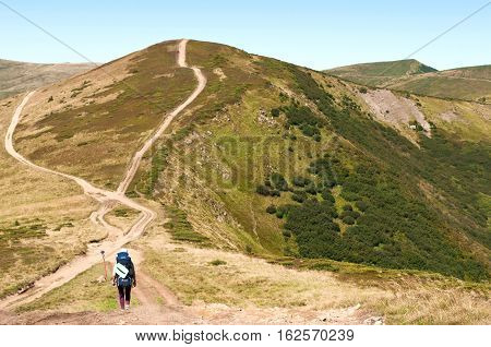 A Girl With A Backpack Heading To A Mountain Hill