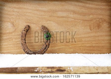 Background with four leaf clover and horseshoe.Horseshoe four leaf clover on wood.