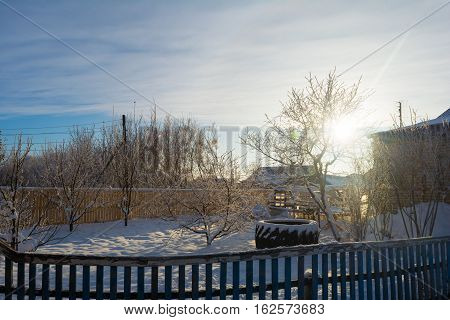 Photo by evening sun in the winter courtyard of rustic house.