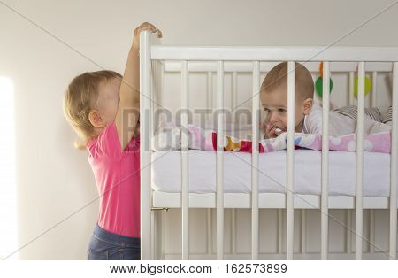 older sister hanged on the crib younger baby