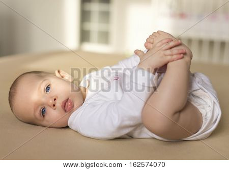 happy baby playing with his small feet