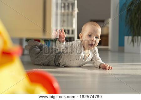 crawling baby has a garage at home under the dresser