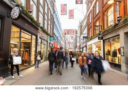 LONDON ENGLAND - DECEMBER 17: People Christmas shopping in motion blur on Carnaby Street London. In London England. On 17th December 2016.