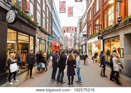 LONDON ENGLAND - DECEMBER 17: People Christmas shopping on Carnaby Street London. In London England. On 17th December 2016.