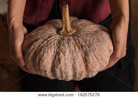 Woman Holds Pumpkin In Her Hands. Close Up Studio Shoot
