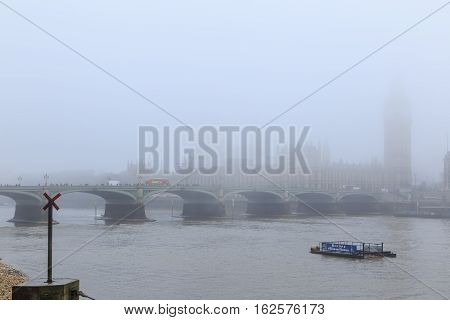 LONDON ENGLAND - DECEMBER 17: Westminster Bridge and the River Thames in the fog. In London England. On 17th December 2016.