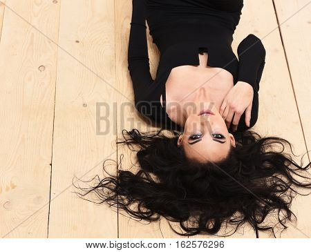 pretty cute sexy girl or beautiful young woman with fashion makeup on serious face and curly long brunette hair in black dress with deep neckline lying upside down on wooden floor background