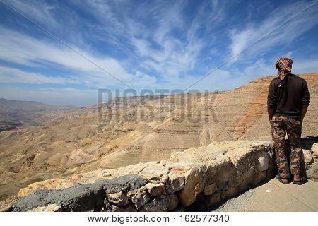 WADI MUJIB, JORDAN - MARCH 6, 2016: A young Jordanian man looking at Wadi Mujib Canyon from Kings Road