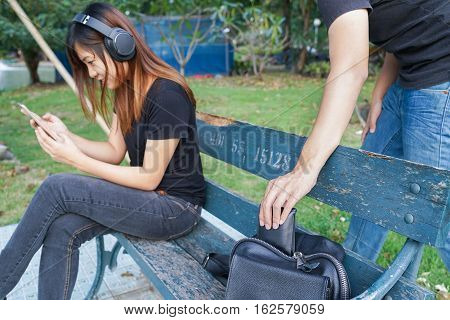 Thief trying to steal and walk away the wallet in the bag while woman using mobile phone and listening to music on sofa in the park