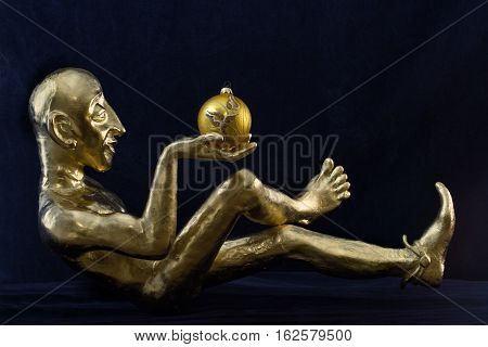 Gilded statuette with Christmas decoration in hand