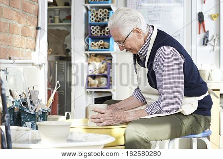 Senior Man Working At Pottery Wheel In Studio