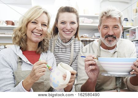 Mature Couple With Teacher In Pottery Class