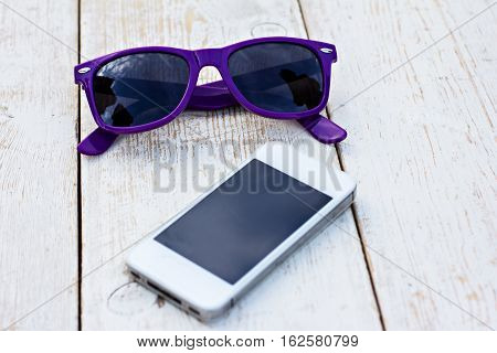 mobile phone and sunglasses on a wooden table