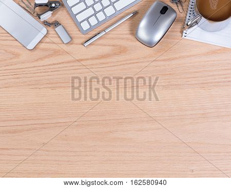 Office desktop with computer keyboard mouse coffee thumb drive pen paper clip staple remover and cell phone. Horizontal format with plenty of copy space