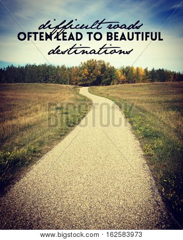Inspirational quote on asphalt pathway road through grass field with colorful trees and sky in background.  Paved trail with slight bend leading into autumn trees. Autumn landscape.Instagram effects.