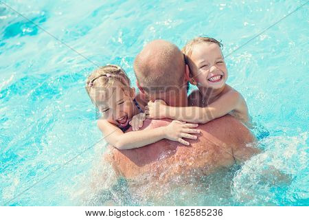 Father playing with two little children in the pool