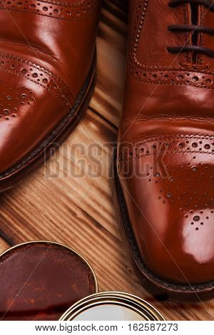 Shoe care. Shoe wax and brushes on wooden surface. Glacage shoes. Oxfords.waxing.Bull shoes.Finger polish.