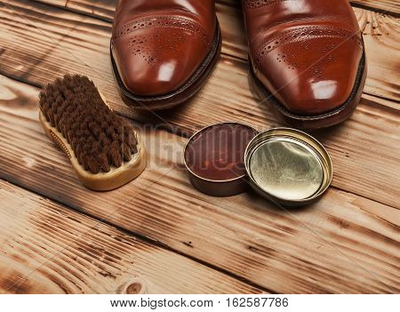 Shoe care. Shoe wax and brushes on wooden surface. Glacage shoes. Oxfords.waxing.Bull shoes.Finger polish. poster