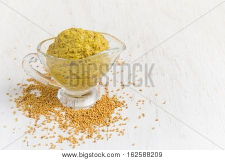 French mustard sauce and mustard seeds on white background copy space