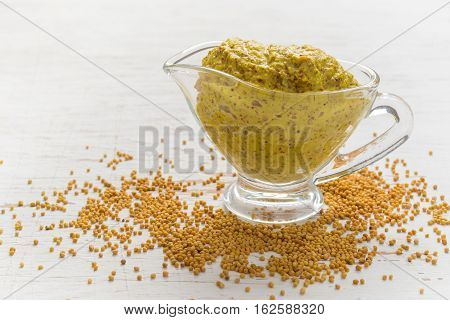 French mustard sauce and mustard seeds on white background.