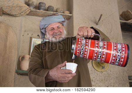 Nizwa Oman December 15th 2016: Omani man serving arabic coffee