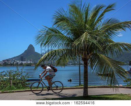 RIO DE JANEIRO, BRAZIL - OCTOBER 31, 2016: Cyclist riding by famous bicycle and running track at residential neighborhood Lagoa, Rodrigo de Freitas Lagoon and Dois Irmaos Mountain on the background