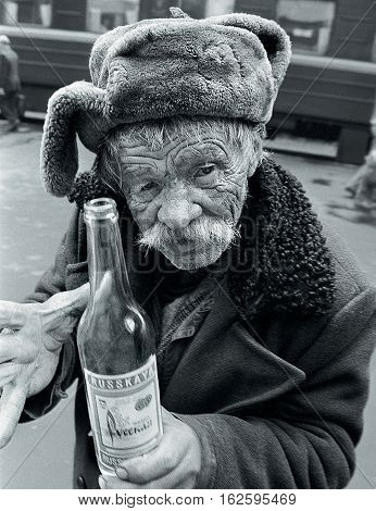 MOSCOW RUSSIA - MARCH 15.2002: An old man with a bottle of vodka at a train station