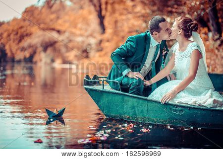 The bride and groom ride at sunset on a boat on the lake, silhouettes. reflexion