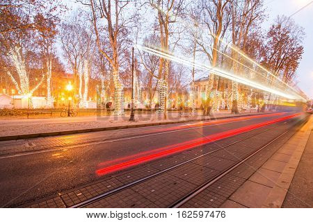 Tram passing Zrinjevac park in Zagreb Croatia during Advent, blue light trail, motion blur