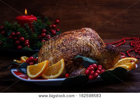 Roasted whole chicken with Christmas decoration. Wooden background.