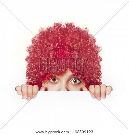The girl in the red wig peeks out from behind banner on white background