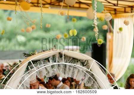 A wedding altar decorated with green bows and straw balls