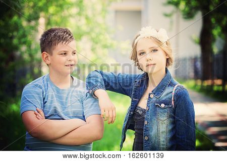 Young Boy and girl Showing Thumbs Up Gesture Outdoors