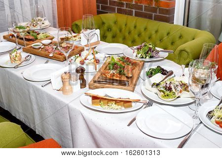 Table with salads and appetizers of seafood and meat on wooden plates in restaurant