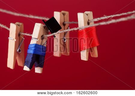 Funny peg characters and clothesline. Man in suit woman red dress. wooden clothespins macro view shallow depth field