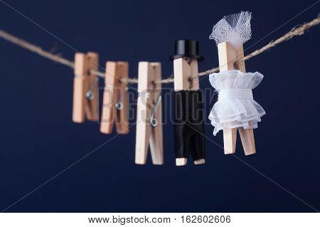 Bride and groom clothespin toys clothesline. Abstract woman in white dress and man character with black suit hat. Love concept photo. Macro view shallow depth of field blue background