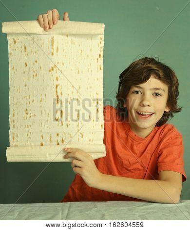 preteen handsome boy hold lavash thin pita bread roll. Smiling boy