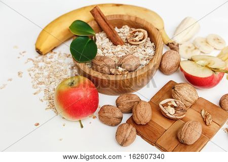 There are Banana,Apple,Walnuts in the Wooden Plate and Rolled Oats.Wooden Spoon,Trivet with Green Leaves,Healthy Fresh Organic Food on the White Background