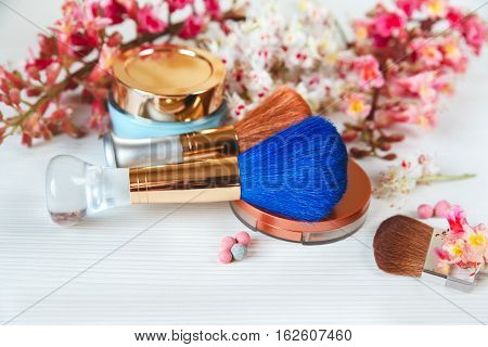 There White and Pink Branches of Chestnut Tree.Bronze Powder with Mirror and Make Up Brown and Blue Brushes with Cream are on White Table.Selective Focus
