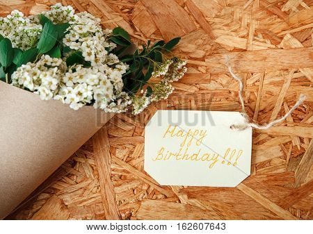 Birthday Card with Bouquet from White Flowers and Green Leaves.Rough Brown Paper on the Texture Wooden Background.Celebrations Wishes.Happy Birthday