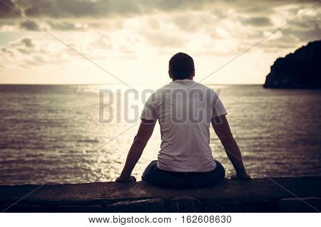 Lonely man looking with hope at horizon with sunlight during sunset with effect of light at the end of tunnel