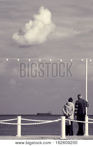 Elderly couple on pier. Grandparents looking at ship at sea under big cloud. Beautiful seascape with cloudy sky. Romantic scene with older lovers. Toned black and white color processing. Nice soft warm light