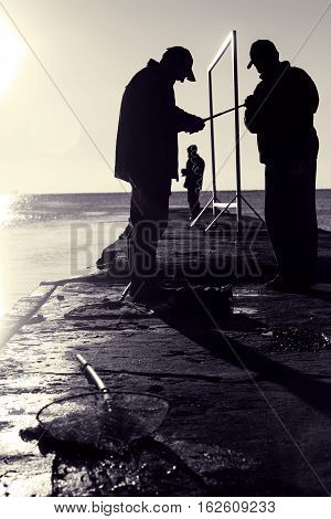 Three fishermen on pier. Silhouettes of people on early sunny morning in backlight. Fishing in sea at sunrise. Toned black and white color processing. Nice soft warm light
