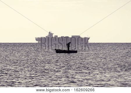 Man and ship. Silhouette of fisherman in boat and huge tanker on horizon. Morning seascape. Fishing in open sea. Loneliness and solitude. Toned black and white color processing. Nice soft warm light