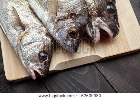 Raw Fish On Wooden Cutting Board