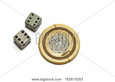 Vintage lucky gambling dice showing a double six and an ornate poker chip showing the number five. Isolated against a white background.